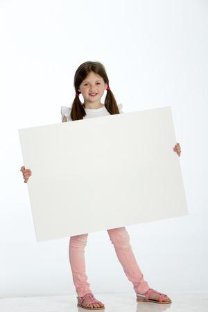 jolie petite fille: Petite fille tenant un signe blanc sur un fond blanc