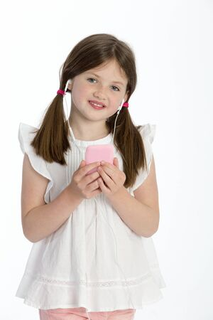 girl looking up: Little girl listening to music through headphones on a smartphone. She is smiling at the camera and standing against a white background.