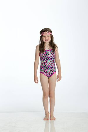 Full length shot of a little girl wearing a swimming costume with goggles on her head. She is smiling at the camera and standing against a white background.