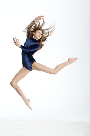 white fly: Gymnast posing in mid air against a white background.