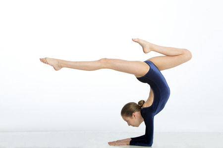 stretchy: Female gymnast balancing in a pose on her arms against a white background. Stock Photo