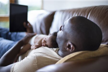 of african descent: A father and newborn daughter at home. He is wearing casual clothing and looking at his digital tablet on the sofa.