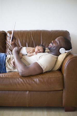 sleeping tablets: Father at home with his newborn baby daughter lying down on the sofa. He has headphones and is looking at his digital tablet. Stock Photo
