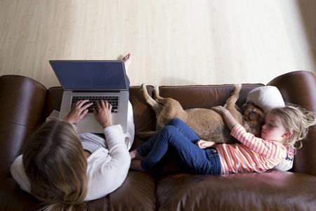 madre trabajadora: Ariel vista de una mujer que usa un ordenador portátil, mientras que su hija está durmiendo al lado de ella, abrazando a su perro mascota. Foto de archivo