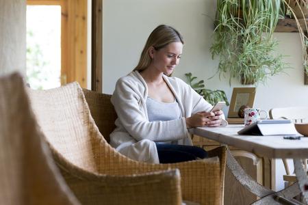 jeune fille: Femme assise � une table dans sa maison en utilisant un smartphone
