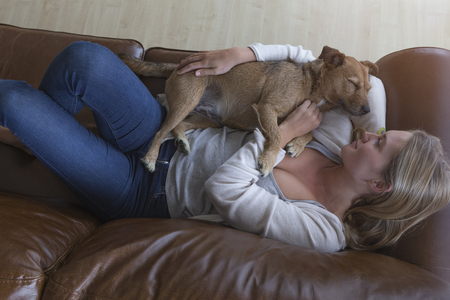 ariel: Ariel view of a woman cuddling her pet dog on a leather sofa.