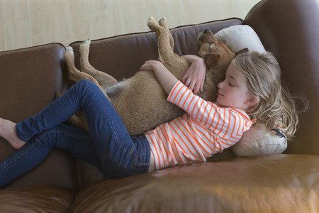 lying on couch: Ariel view of a young girl cuddling her pet dog on a sofa a t home.