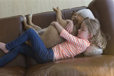 T 家のソファの上の彼女のペットの犬を抱きしめる少女のアリエル ビュー。