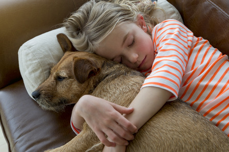Young girl cuddling her pet dog on a sofa at home.