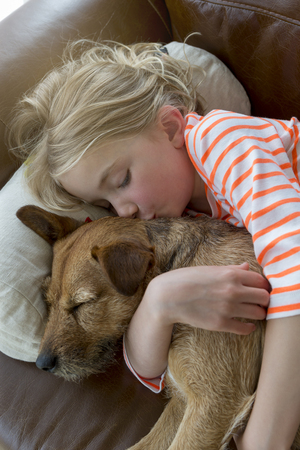 pets: Young girl cuddling her pet dog on a sofa at home.