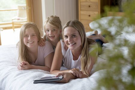 children love: Sisters lying on a bed in their home with a digital tablet, smmiling for the camera.