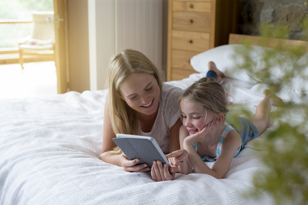 en suite: Mother and daughter lying on a bed at home together, using a digital tablet. Stock Photo