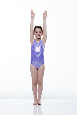 leotard: Portrait of a young female gymnast taken in the studio on a white background. She is wearing a leotard and smiling at the camera. Stock Photo