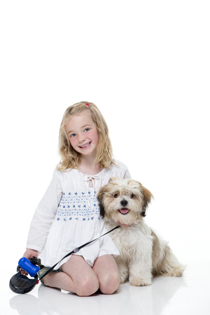 girl sitting down: Portrait of a little girl sitting down with her dog. She is looking at the camera and smiling.
