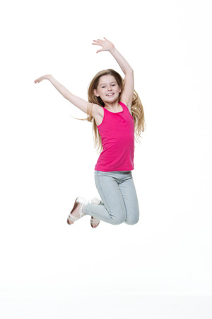 on a white background: Portrait of a happy little girl jumping in the air against a white background.
