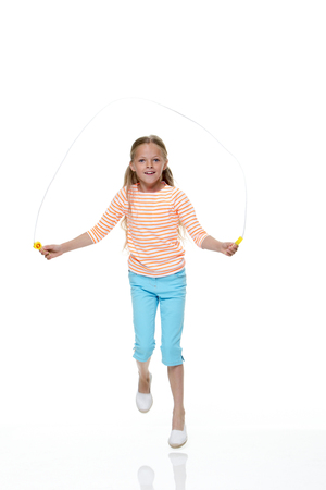 saltar la cuerda: Retrato de una chica joven que salta con un fondo blanco. Ella lleva ropa casual y mirando a la c�mara y sonriendo.