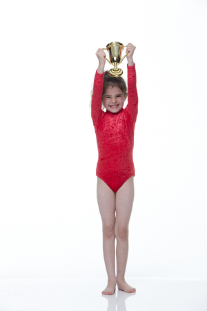 leotard: Young gymnast in a red leotard holding up a trophy on a white background. She is looking at the camera and smiling. Stock Photo