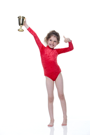 holding up: Young gymnast in a red leotard holding up a trophy on a white background. She is looking at the camera and smiling. Stock Photo