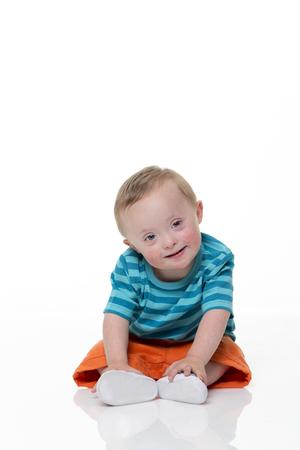 흰색 배경에 앉아 아름 다운 downsyrome 아기의 초상화.