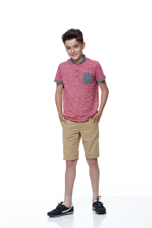 boy shorts: Young male dressed in casual clothing with a white background. he is looking at the camera and smiling. Stock Photo