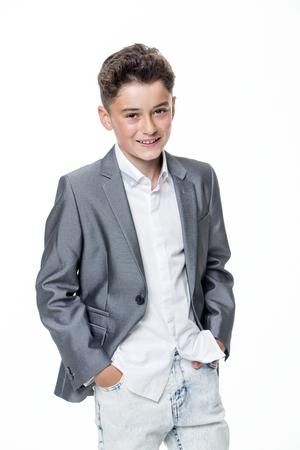 niño: Adolescente joven feliz vestida elegantemente sobre un fondo blanco. Él está mirando a la cámara y sonriendo.