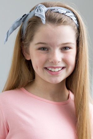 A portrait of a young girl with a grey background. She is looking at the camera and smiling.