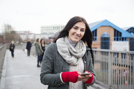 handheld device: Attractive young woman smiling for the camera with a smartphone in her hands.