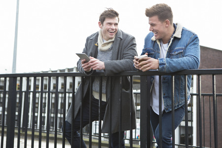 men talking: Two young men talking in the city. One is holding a smartphone, the other is holding a disposable coffee cup.