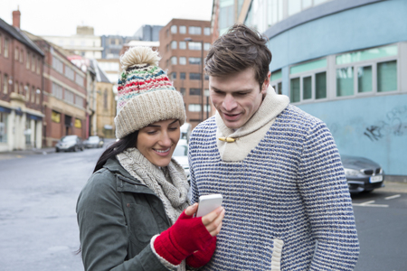 handheld device: Young couple standing together in the cold weather, looking at a smartphone