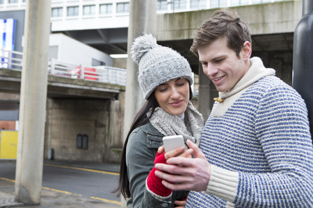 handheld device: Young couple taking a selfie on a smartphone in the city Stock Photo