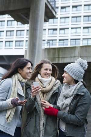 real: Three young women in the city, looking at something on a smartphone. Stock Photo