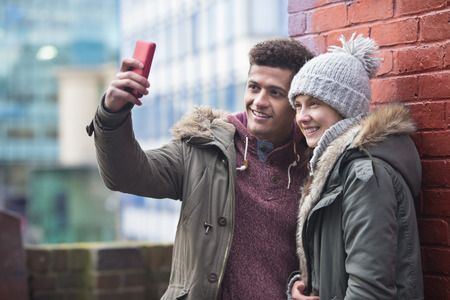 handheld device: Young couple taking a selfie in the city.