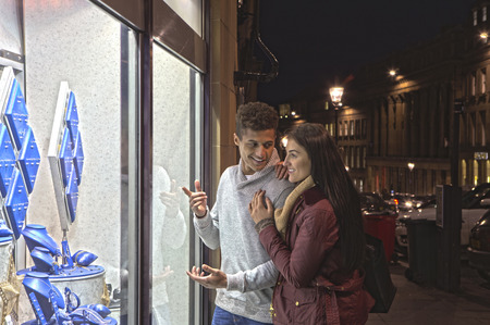 winter couple: Young couple looking at jewellery through a shop window in the city at evening. Stock Photo