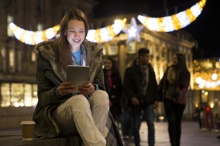 people: Young woman looking at a digital tablet in the city at evening Stock Photo