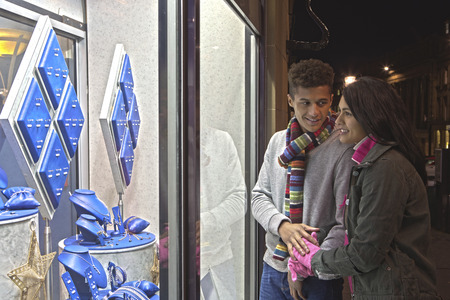 gold ring: Young couple looking at jewellery through a shop window in the city at evening. Stock Photo
