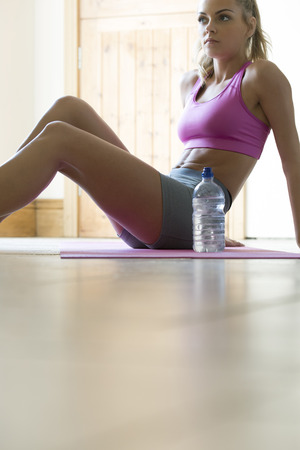 workouts: Young woman having a short break from her home workouts. She is sitting on an exercise mat with a bottle of water. Stock Photo