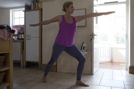 body toning: Mature woman in her home, doing yoga on an exercise mat.