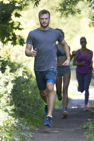 fitness hombres: Tres personas de diferentes edades que se ejecutan a lo largo de un sendero en el bosque