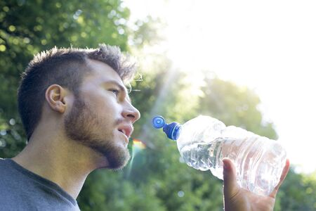whilst: Young man having a drink of water whilst out running