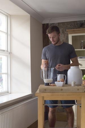 muscle training: Junger Mann mit einem Protein-Shake zu Hause.