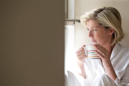 Zralá žena se těší ranní pohled z jejího okna s šálkem čaje.