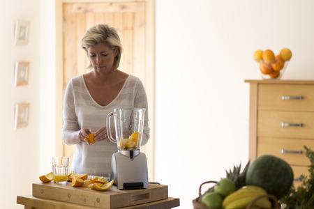 naranja: Mujer madura poner gajos de naranja en una licuadora para hacer un batido de frutas. Foto de archivo