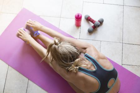 forme et sante: Jeune femme d'étirement après une séance d'entraînement à la maison