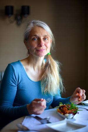 mujer golpeada: Retrato de una mujer madura que goza de un plato calamares