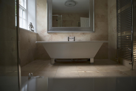 en suite: Shot of an elegantly designed bathroom. A large stand alone bath stands in the middle of the image with a big mirror above it. The bathroom is marble tiled, with a buddha ornament on the window sill.