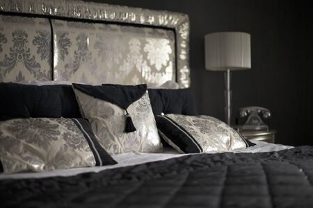 master bedroom: Luxury bed with dark bedding and floral pillows and head board in a master bedroom