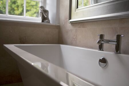 en suite: Close up of a luxury stand alone bath in a marble tiled bathroom. A window can be seen with a buddha ornament standing on the sill