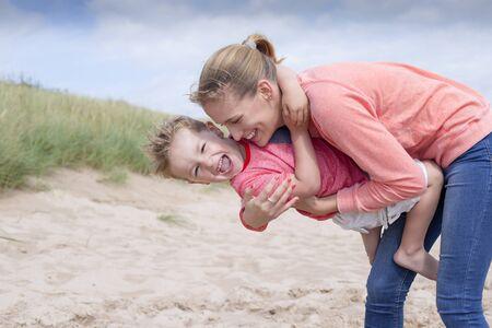 mama e hijo: Joven madre y su hijo en la playa. Ella lo está sosteniendo y ambos están riendo.