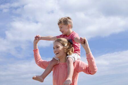 niños rubios: Madre e hijo en el fondo de cielo azul brillante. Se están riendo y sonriendo.
