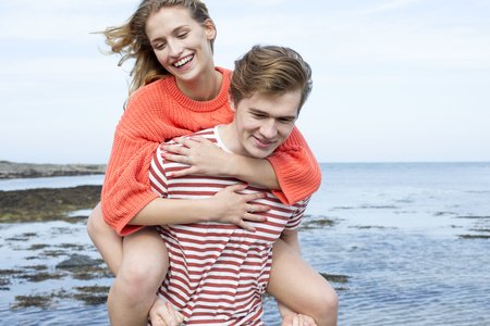 piggyback: Beautiful young couple at the beach. They are smiling and the young woman is having a piggyback from her boyfriend.